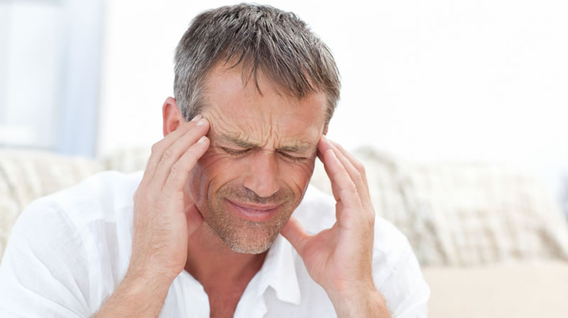 TMJ Therapy - Image of a man holding his face in pain